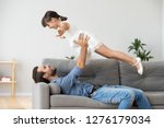 smiling father lying on couch... | Shutterstock . vector #1276179034