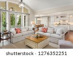 Small photo of Beautiful Living Room, Kitchen, and Dining Room in New Luxury Home with Open Concept Floor Plan. Living Room Has Elegant Furniture with French Doors Leading to Deck. Kitchen Features Large Island.