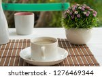 coffee cup on wood table in the ... | Shutterstock . vector #1276469344