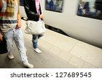 Subway passengers walking along platform - stock photo