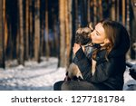 Stock photo young woman is holding a french bulldog puppy in her arms at winter owner is kissing her dog 1277181784