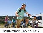 family riding bikes in... | Shutterstock . vector #1277271517