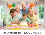 boy blowing out candles on cake ... | Shutterstock . vector #1277274787