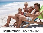 family in deckchairs on sandy... | Shutterstock . vector #1277282464
