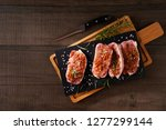 slices of a raw pork fillet on... | Shutterstock . vector #1277299144