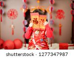 Small photo of Chinese baby girl traditional dressing up with a FU means lucky red envelope against FU means lucky ornament background