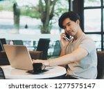 smart asian man using laptop in ... | Shutterstock . vector #1277575147