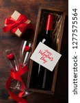 Stock photo valentine s day greeting card with red wine bottle and love gift box on wooden background top view 1277575564