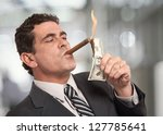 Small photo of Rich businessman lighting cigar with $100 dollar bill