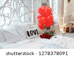 Stock photo celebrating saint valentine s day with red roses on bed and air balloons in shape of heart on the 1278378091