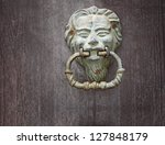 Old green Door knoker handle on an old wooden door - stock photo