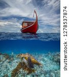 Small photo of Maldivian exotic diving boat and sea turtle underneath in water background underwater split shot