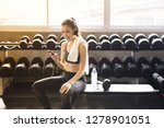 Fit Woman Using Headphone And...