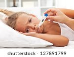 Sick little girl holding thermometer laying in bed with grumpy face - stock photo