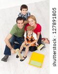 Happy family with paint preparing to redecorate their home - together with the kids - stock photo