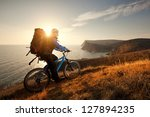 young man tourist on a bicycle... | Shutterstock . vector #127894235