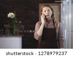 female florist in a brown apron ... | Shutterstock . vector #1278979237