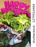 Small photo of REDWOOD FALLS, MINNESOTA USA - MARCH 13, 2016: Garish happy birthday bouquet written with large violet plastic letters.