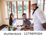 male chef serving food to young ... | Shutterstock . vector #1279899304