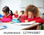 schoolgirl sitting at a desk in ... | Shutterstock . vector #1279943887