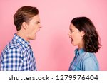 Profile side view portrait of attractive mad fury furious anxious gloomy couple looking at each other breaking up conflict opened mouth isolated over pink pastel background