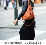Woman with bag crossing street - stock photo