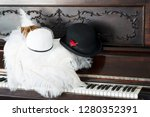 Fancy hats on an old 1890 piano with keys showing. White womens derby hat and a black mens bowler derby hat.