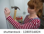 female carpenter hammering nail ... | Shutterstock . vector #1280516824