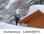 a man removes heavy snow from... | Shutterstock . vector #1280558971