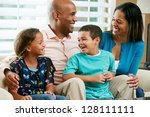 family sitting on sofa together | Shutterstock . vector #128111111