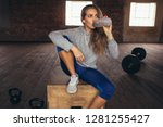 woman sitting on a box at gym... | Shutterstock . vector #1281255427