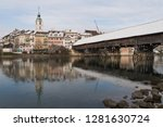 City tower old wooden bridge (AD 1295) and Aare river of Olten Switzerland with Jura mountains during Winter with snow on rooftops and railway station which is a central junction for the SBB
