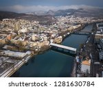 Aerial view of medieval city Olten with old wooden bridge, railway station, Jura mountains, Aare,  Kantonsschule Olten during Winter with snow on rooftops