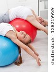 Stretching gymnastic exercise - woman with little girl using large balls - stock photo