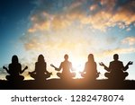 silhouette of people doing yoga ... | Shutterstock . vector #1282478074