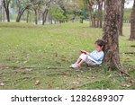 adorable little girl reading a...   Shutterstock . vector #1282689307