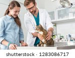 doctor and girl looking at cat... | Shutterstock . vector #1283086717