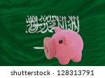 Piggy rich bank in front of national flag of  saudi arabia symbolizing saving and accumulating funds as good financial habit - stock photo