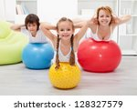 Kids and woman doing gymnastic at home - with large balls - stock photo