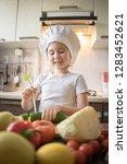 little girl cuts fruit in... | Shutterstock . vector #1283452621