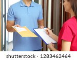 woman receiving padded envelope ... | Shutterstock . vector #1283462464