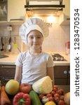 little girl cuts fruit in... | Shutterstock . vector #1283470534