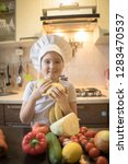 little girl cuts fruit in... | Shutterstock . vector #1283470537