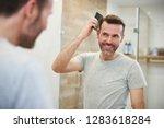 man combing his hair in the... | Shutterstock . vector #1283618284
