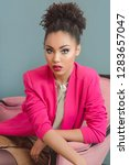 Small photo of beautiful attractive young woman (mixed rase) with make up and in pink blazer sitiing on the chair