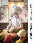 little girl cuts fruit in... | Shutterstock . vector #1283677591
