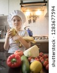 little girl cuts fruit in... | Shutterstock . vector #1283677594