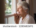 happy senior woman standing at... | Shutterstock . vector #1283682691