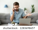 Small photo of Angry man talking on phone disputing over computer laptop problem, stressed unsatisfied impatient customer arguing by mobile solving online difficulty with technical support complain on bad service