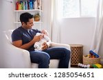 smiling hispanic father holding ... | Shutterstock . vector #1285054651